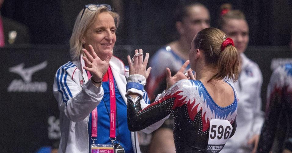 A francesa Anne Kuhm comemora sua performance com a treinadora após a apresentação nas barras assimétricas, na eliminatória do Mundial de ginástica artística em Glasgow