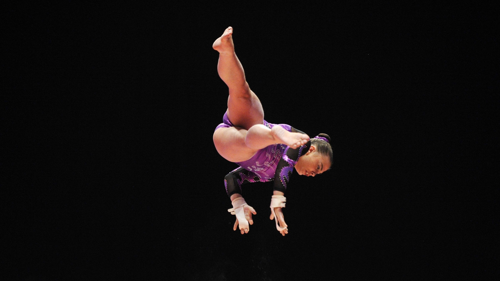 Detalhe do voo de Madeleine Leydin, da Austrália, em sua apresentação nas barras assimétricas, na eliminatória do Mundial de ginástica em Glasgow