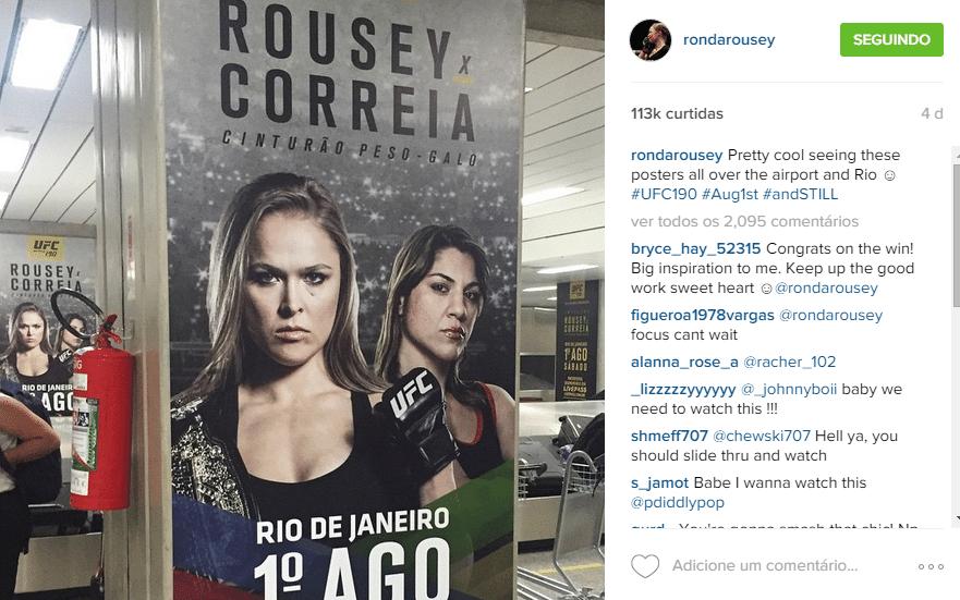 Ronda Rousey comemora ver propagandas no aeroporto do Rio, na chegada ao Brasil, quinta-feira.