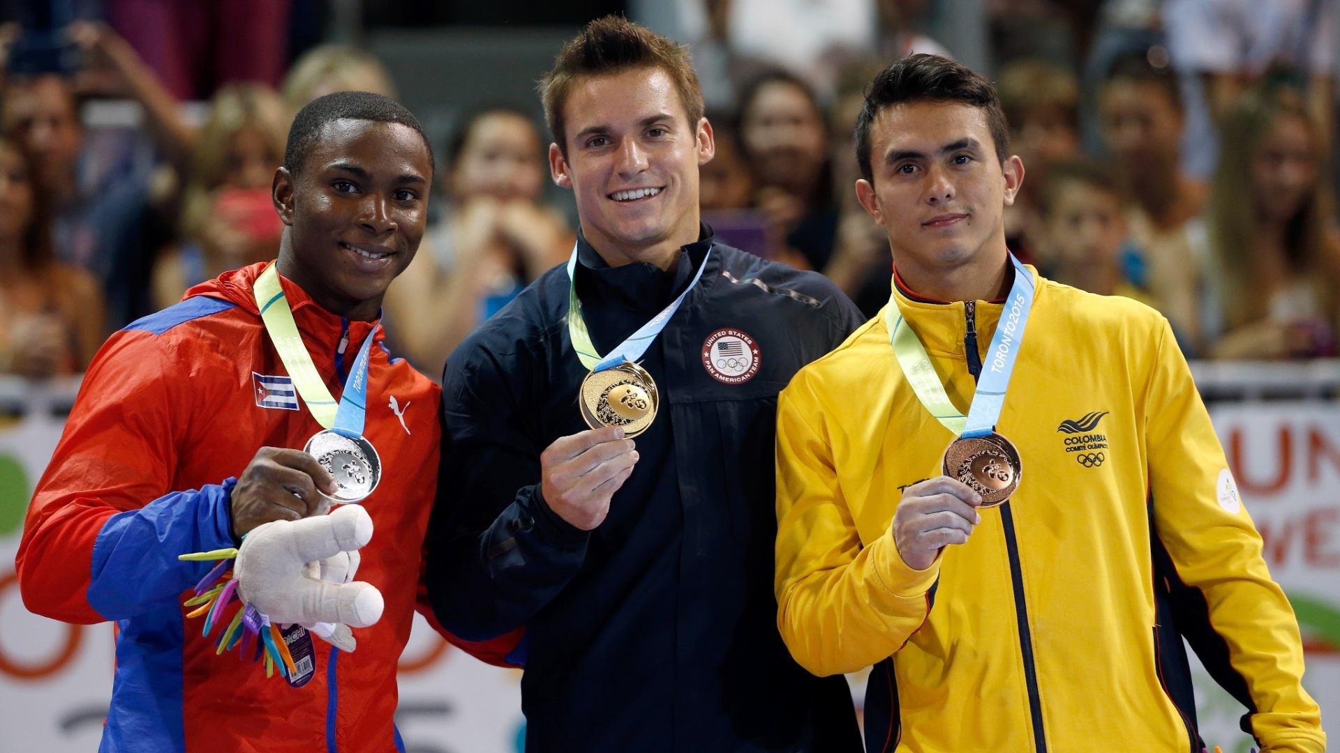 Manrique Larduet, de Cuba, Samuel Mikulak, dos Estados Unidos, e Jossimar Calvo Moreno, da Colômbia, no pódio do individual geral da ginástica artística
