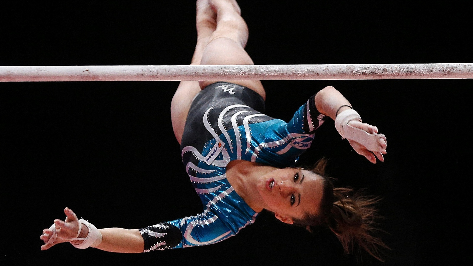 Larissa Iordache, da Romênia, executa uma pirueta em sua apresentação nas barras assimétricas durante a final individual geral do Mundial de ginástica