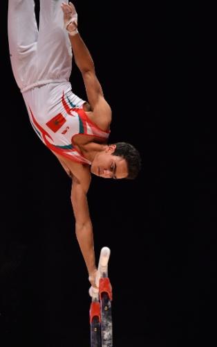 Hamza Hossaini, ginasta marroquino, se apresenta nas barras paralelas na eliminatória do Mundial de ginástica artística