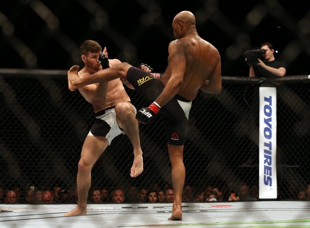 Anderson Silva (dir.) tenta chute alto contra Michael Bisping, na luta principal do UFC em Londres, neste sábado (27)