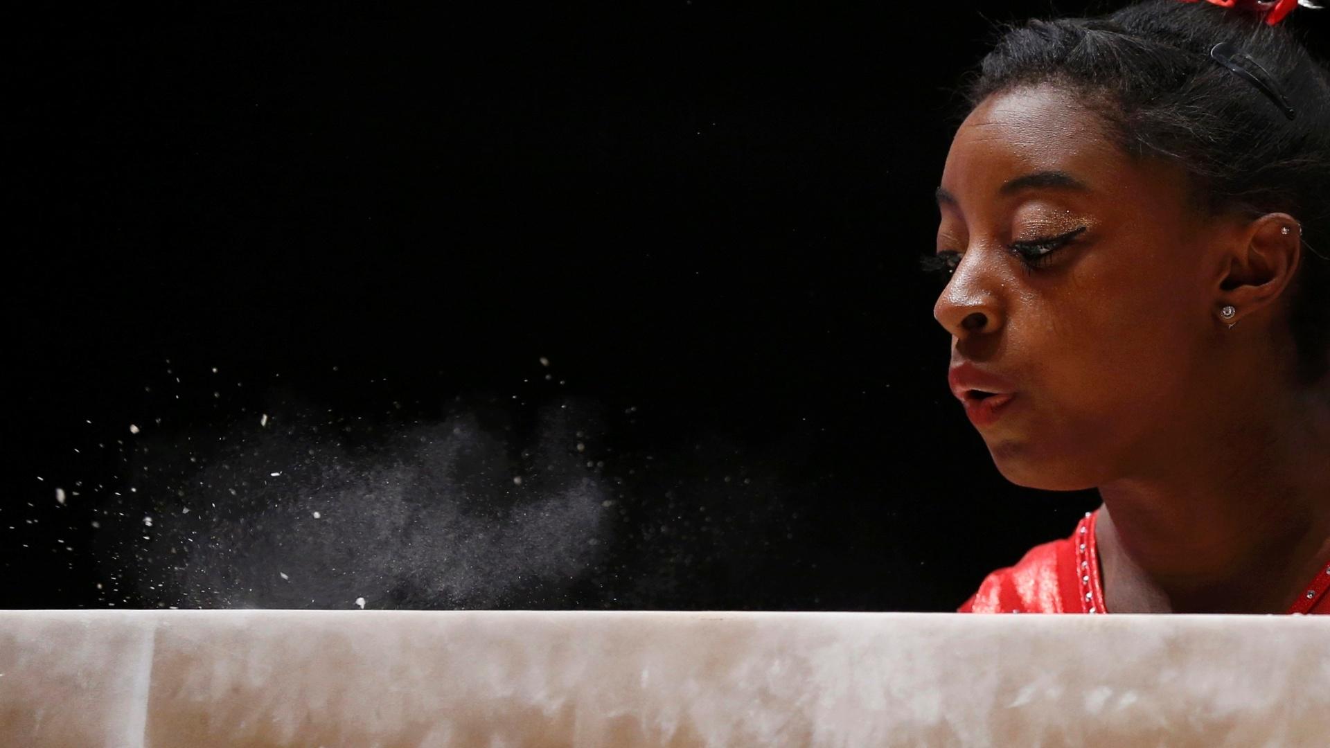 Simone Biles, dos EUA, assopra o giz da trave antes da sua apresentação no Mundial de ginástica