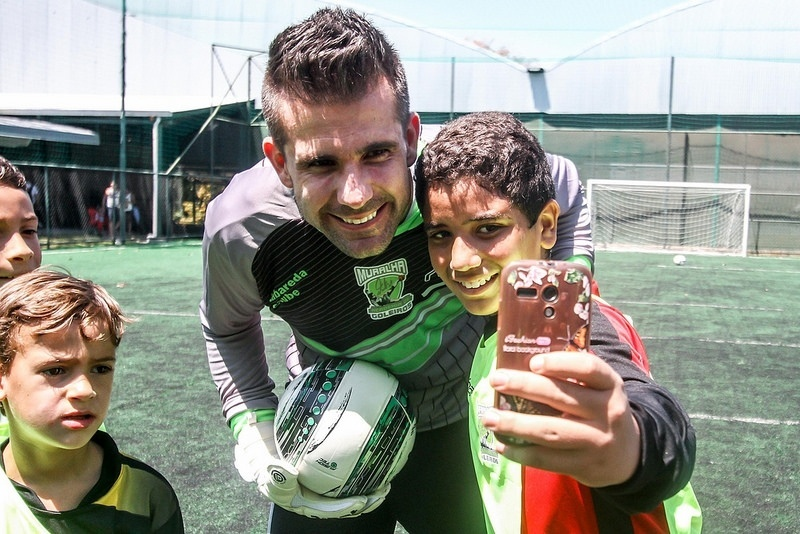 Pequeno fã aproveita aula para tirar uma foto com o goleiro Victor, do Atlético-MG