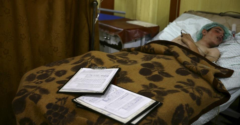 Jovem sírio repousa enquanto recebe tratamento em um dos abrigos transformados provisóriamente em hospitais onde médicos e voluntários trabalham em condições precárias na cidade síria de Douma