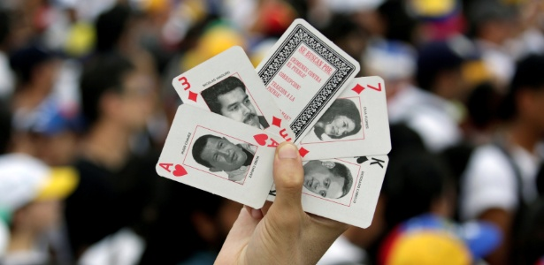 Manifestante mostra cartas de baralho com as imagens de Hugo Chávez e Nicolás Maduro durante protesto de opositores ao governo venezuelano, em Caracas