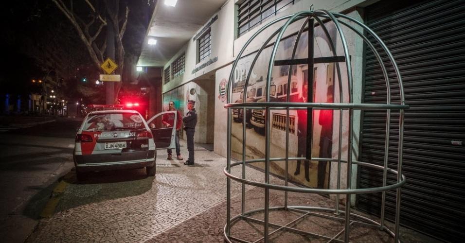 15.ago.2015 - Uma cruz pendurada dentro de uma gaiola foi colocada em frente ao prédio do DPCC (Departamento de Polícia de Proteção à Cidadania), no centro de São Paulo, em um ato de protesto e solidariedade às famílias das vítimas de ataques em Osasco e Barueri.
