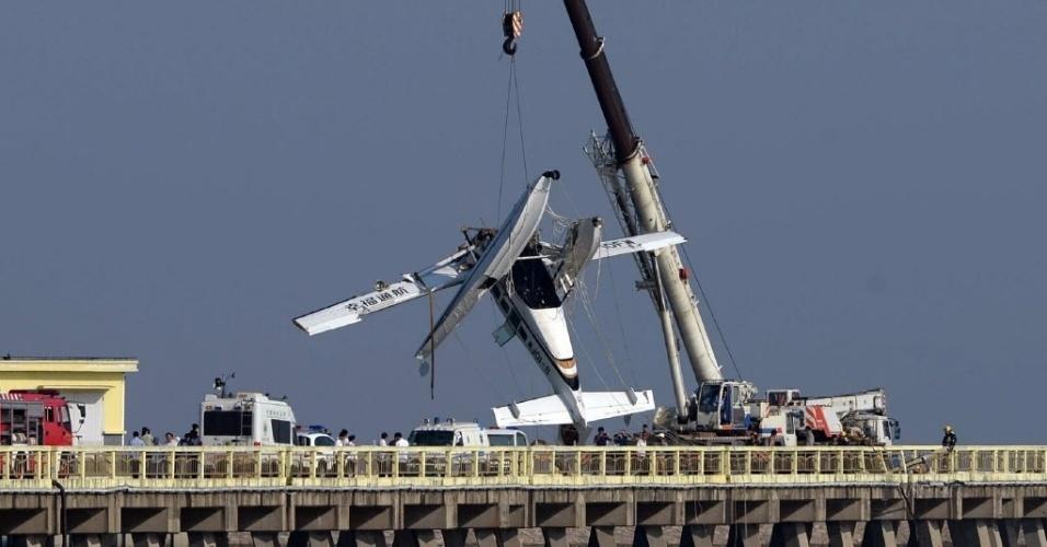 20.jul.2016 - Um guindaste levanta o hidroavião que bateu em uma ponte da estrada em Jinshan, Xangai, na China. De acordo com a imprensa local, ao menos cinco pessoas morreram no acidente, que aconteceu cerca de dez minutos depois da decolagem em uma praia durante o voo inaugural do avião anfíbio