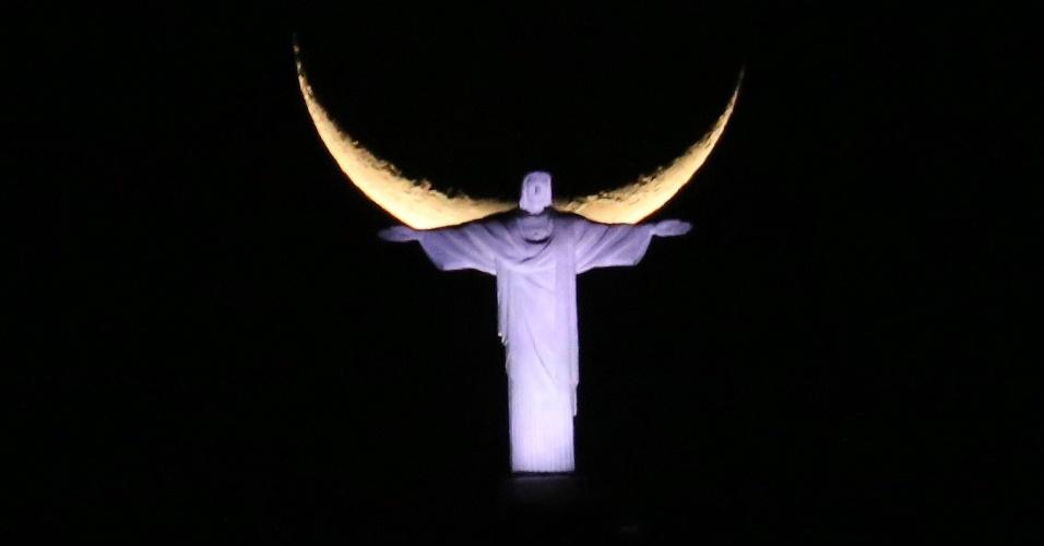 17.set.2015 - Cristo Redentor é visto com lua ao fundo na noite desta segunda-feira (16) no Rio de Janeiro (RJ)