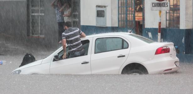 22.dez.2015 - Homem foge de carro ilhado durante alagamento em Santana do Livramento (RS) na terça-feira