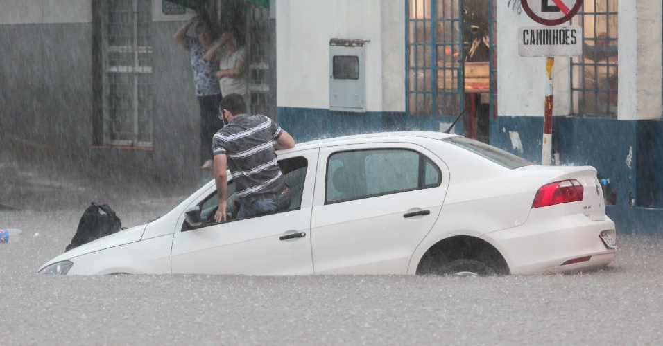 22.dez.2015 - Homem foge de carro ilhado durante alagamento em Santana do Livramento (RS) nesta terça-feira. As chuvas que atingem o Rio Grande do Sul no fim do ano já deixaram 443 famílias desalojadas e 23 desabrigadas