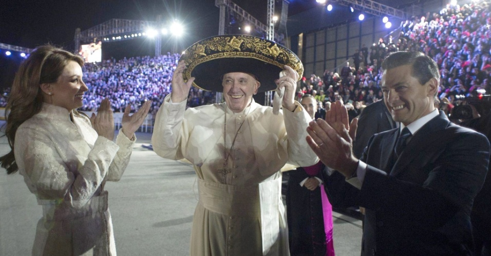 12.fev.2016 - Papa Francisco usa um sombrero ao ser recebido pelo presidente do México, Enrique Pena Nieto, e a primeira-dama, Angelica Rivera, na chegada do pontífice ao Aeroporto Internacional Benito Juarez, na Cidade do México. O papa vai visitar quatro Estados mexicanos até quarta-feira (17)