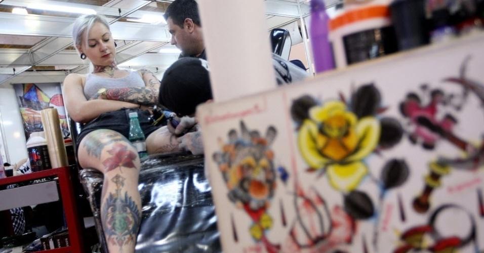 24.jul.2015 - Mulher recebe tatuagem na perna durante a quinta edição da Tattoo Week, que começou hoje e vai até o domingo (26). O evento conta com 460 estandes de artistas nacionais e estrangeiros e acontece no pavilhão Azul do Expo Center Norte, na Vila Guilherme, zona Norte de São Paulo. Neste sábado (25), acontece o concurso Miss Tattoo Week SP 2015