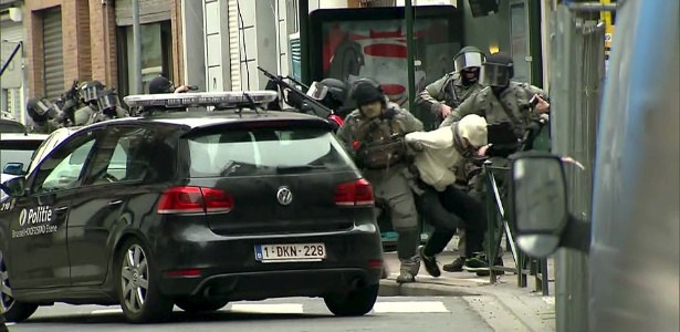 Salah Abdeslam (em roupas claras), suspeito foragido de participação em ataques a Paris, é preso por policiais belgas, em Molenbeek, próximo a Bruxelas (Bélgica)
