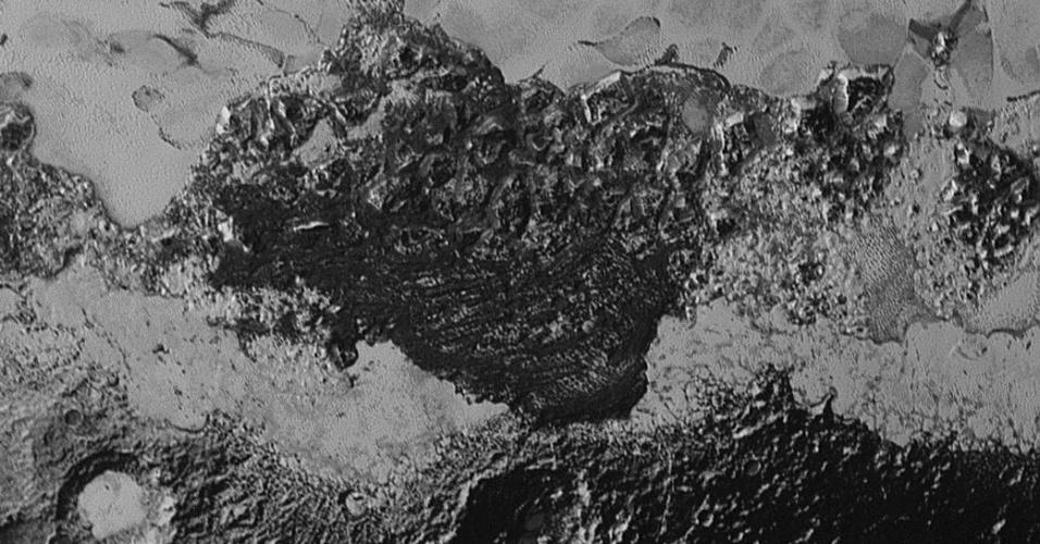 21.set.2015 ? A Nasa (Agência Espacial Norte-americana) divulgou imagens em alta resolução de Plutão tiradas pela nave New Horizons que mostram, na parte mais clara, a planície gelada do solo e, na parte escura da foto, um terreno com montanhas, crateras, possíveis dunas e outras formações geológicas enigmáticas