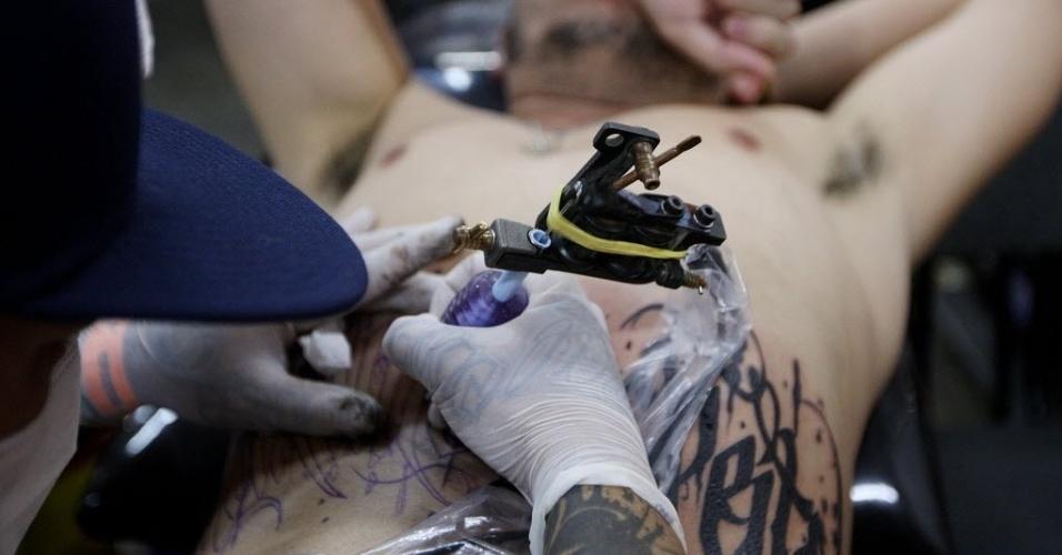 24.jul.2015 - Tatuador faz desenho na barriga de um participante da quinta edição da Tattoo Week, que começou hoje e vai até o domingo (26). O evento conta com 460 estandes de artistas nacionais e estrangeiros e acontece no pavilhão Azul do Expo Center Norte, na Vila Guilherme, zona Norte de São Paulo. Neste sábado (25), acontece o concurso Miss Tattoo Week SP 2015