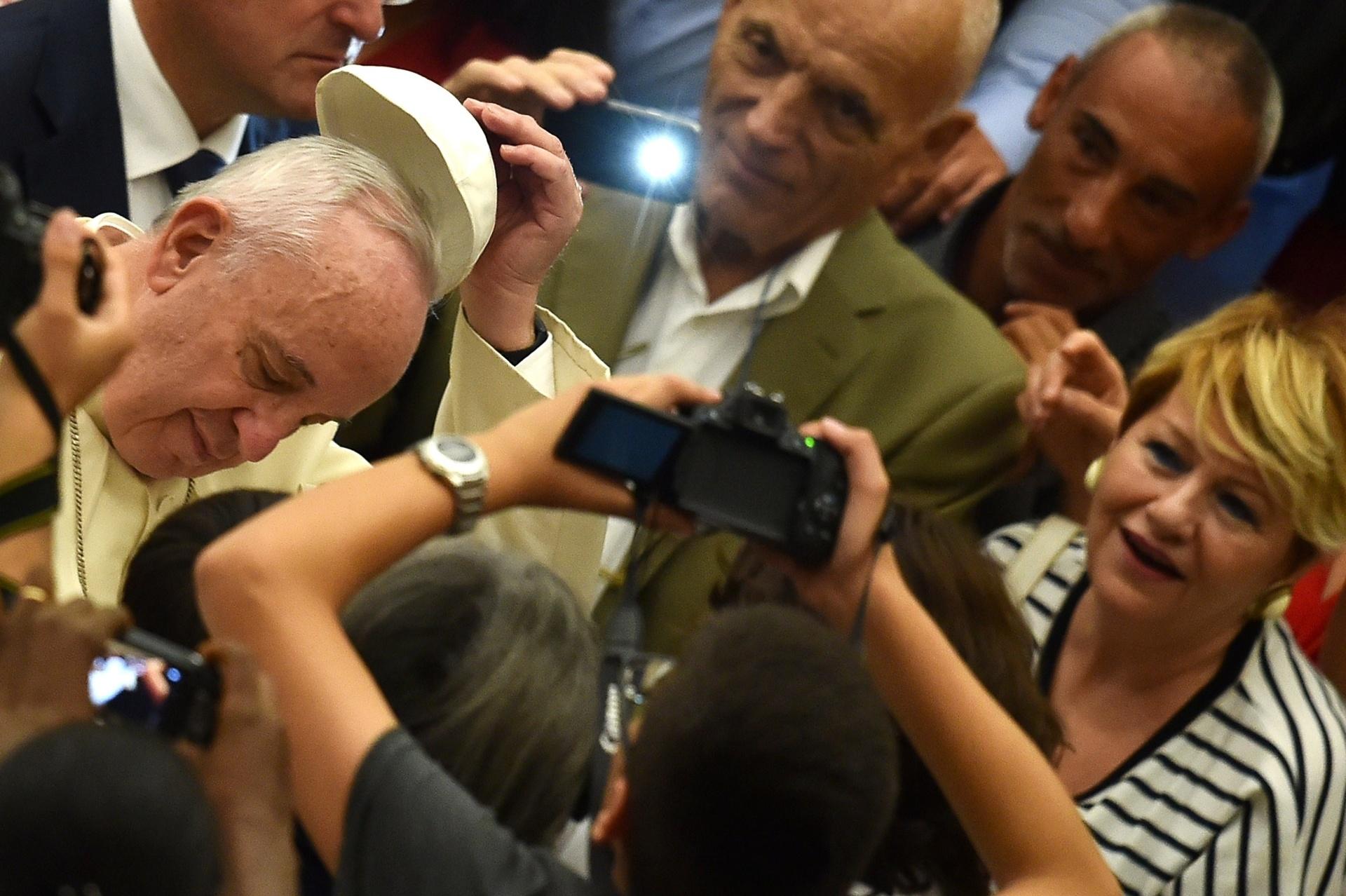 12.ago.2015 - Papa Francisco tira o solidéu em cumprimento aos fiéis presentes na Sala Paulo VI para sua audiência semanal