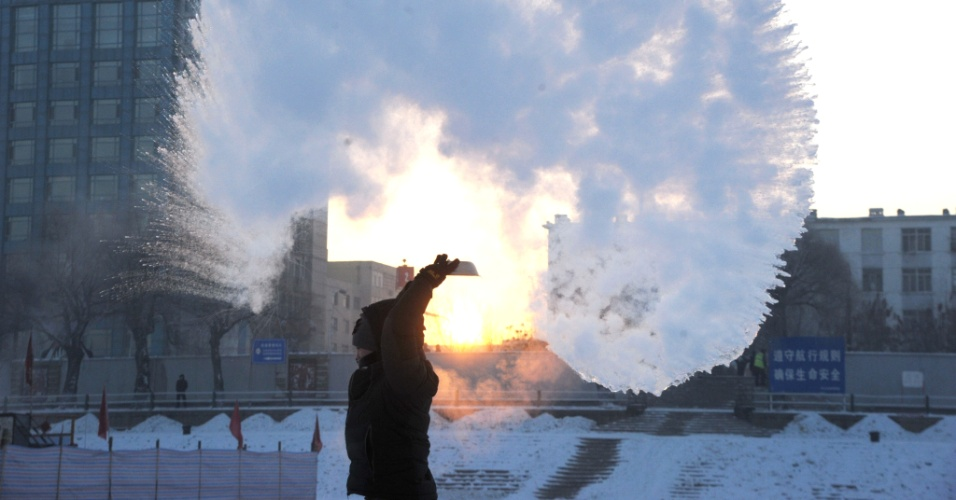 21.jan.2016 - Com os termômetros marcando -30º C em Harbin, no nordeste da China, a água quente congela logo após ser lançada ao ar por um morador da cidade