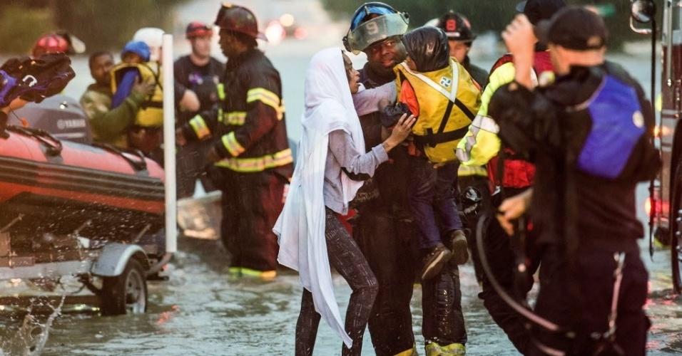 4.out.2015 - Charlene Stennis pega seu filho das mãos de um bombeiro após ser resgatada de carro submerso em enchente em Columbia, na Carolina do Sul (EUA). O presidente Barack Obama declarou estado de emergência na região devido aos alagamentos