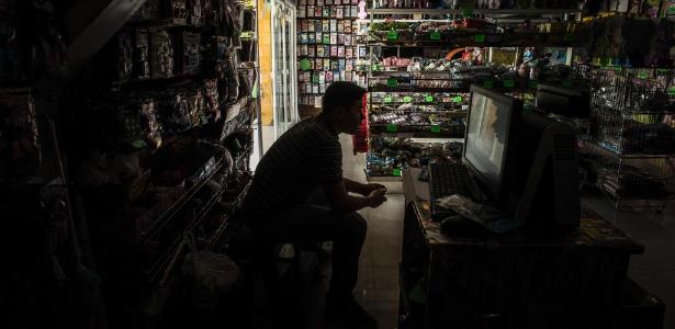 Kevin Munoz espera por clientes no escuro em sua loja, durante apagão em Caracas, na Venezuela