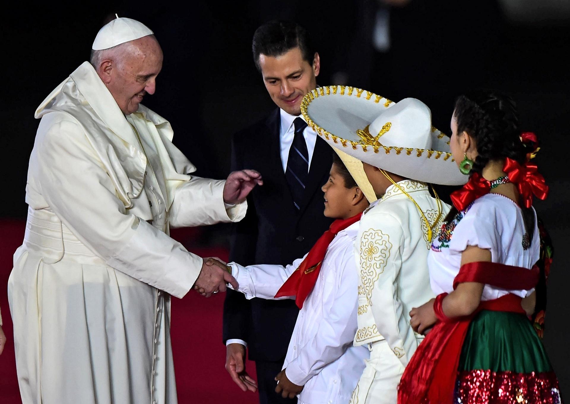 13.fev.2016 - Ao lado do presidente Enrique Pena Nieto, o Papa Francisco cumprimenta crianças mexicanas logo após sua chegada ao aeroporto internacional Benito Juarez, na Cidade do México. O papa começou nesta sexta-feira (horário local) sua primeira visita ao México, onde passará os próximos cinco dias
