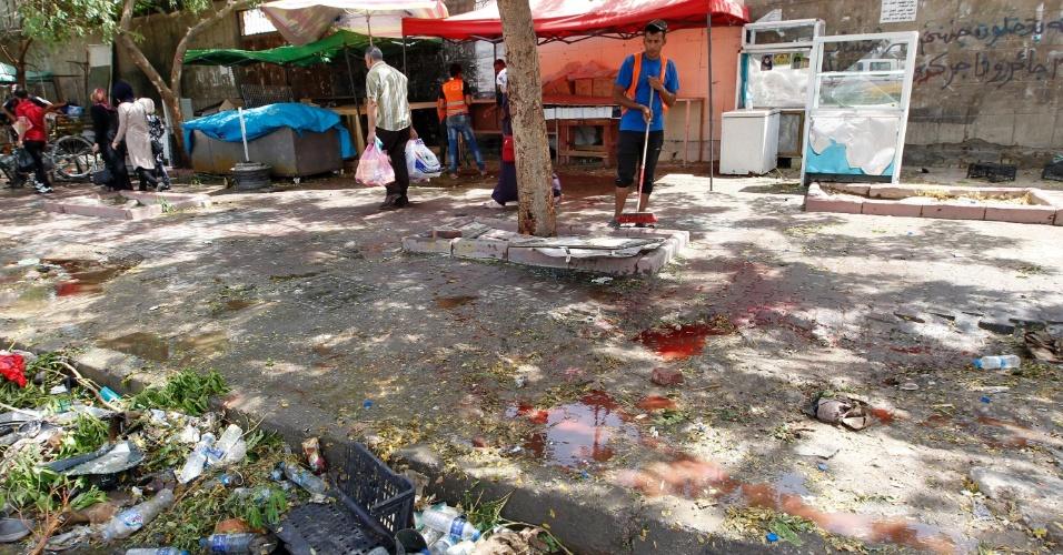 24.jul.2016 - Homem limpa o chão ensanguentado no local onde ocorreu um ataque suicida que deixou pelo menos 21 mortos e 35 feridos, na região de maioria xiita de Al Kazemiya, no norte de Bagdá. O atentado foi reivindicado pelo Estado Islâmico, que considera membros da maioria xiita do Iraque hereges