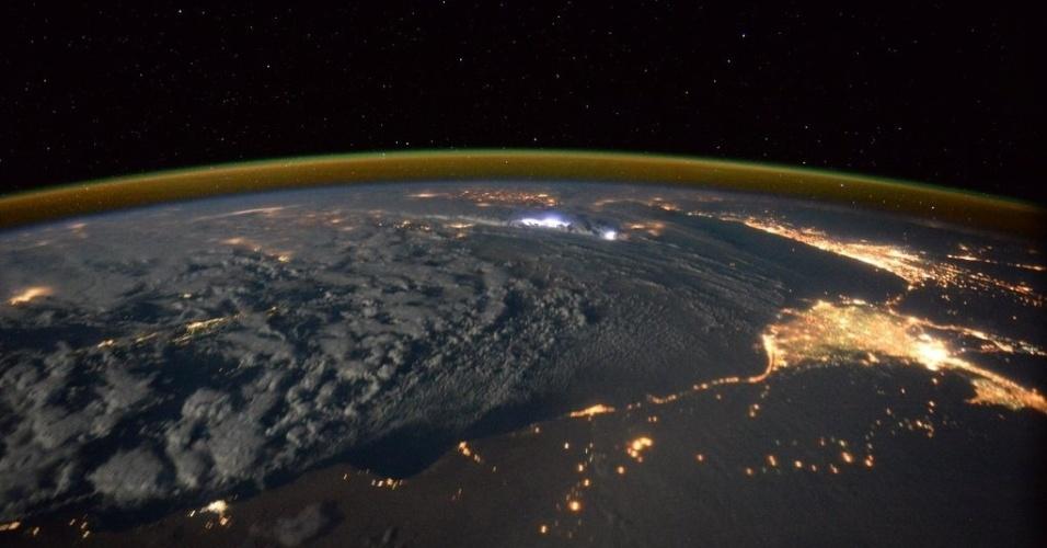 19.jan.2016 - O astronauta britânico Tim Peak, a bordo da ISS (Estação Espacial internacional) fotografou as luzes do Cairo, no Egito. O contorno verde na Terra é efeito da atmosfera. A foto foi publicada no perfil de Peak no Twitter