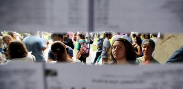 Estudante procura o nome em lista de vestibular para a USP, com o sonho de ingressar no ensino superior