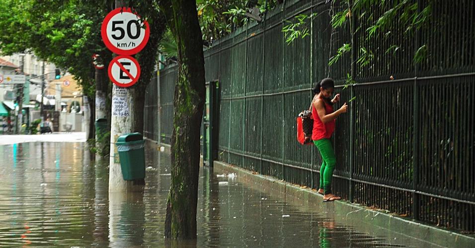27.jan.2016 - Mulher se equilibra em muro na rua Palestra Itália, em Perdizes, zona oeste de São Paulo, que ficou alagada após forte temporal que atingiu a capital paulista. Até as 17h, já havia mais de 30 pontos de alagamento na cidade