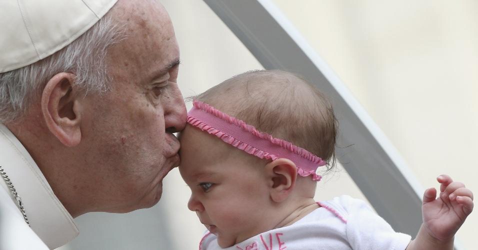 14.out.2015 - Papa Francisco beija bebê na chegada à audiência semanal na Praça de São Pedro, no Vaticano