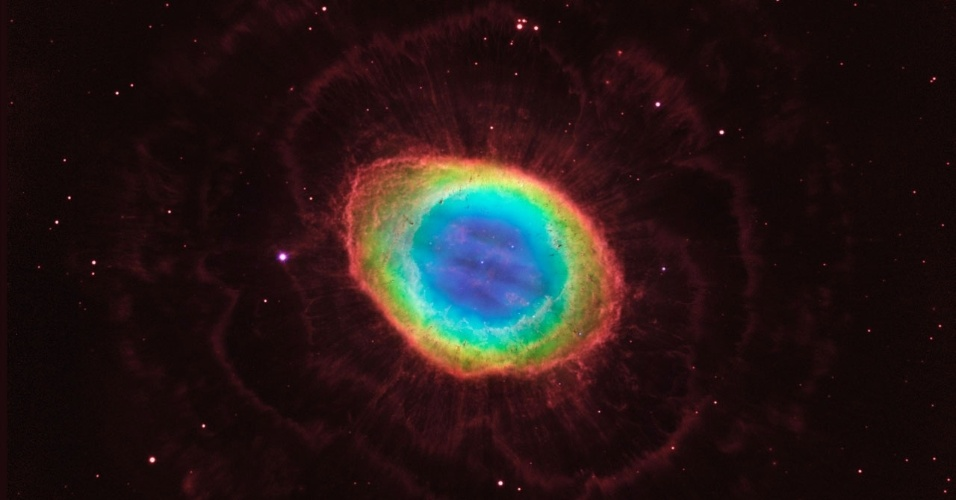 """23.mai.2013 - Cientistas descobrem real formato da Nebulosa do Anel, que não é """"oca"""" como se imaginava. Usando imagem composta de observações na luz visível feita pelo Hubble e de dados infravermelhos do Grande Telescópio Binocular no solo do Arizona, os pesquisadores puderam ter uma boa imagem da nebulosa, que está a 2.000 anos-luz da Terra, na constelação de Lira. A imagem revela um gás brilhante ao redor da estrela similar ao Sol que está morrendo em seu centro, e não apenas formando um """"anel"""" como se pensava. Com os novos dados foi possível construir o mais preciso modelo 3D da nebulosa, com sua complexa estrutura"""
