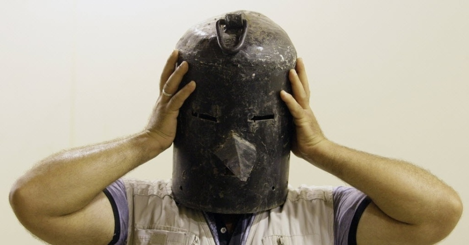 24.mai.2013 - Visitante de galeria em Bagdá, no Iraque, experimenta máscara de tortura utilizada no regime de Saddam Hussein. Saddam governou o Iraque de 1979 a 2003, quando invsão de tropas norte-americnas levou a sua queda