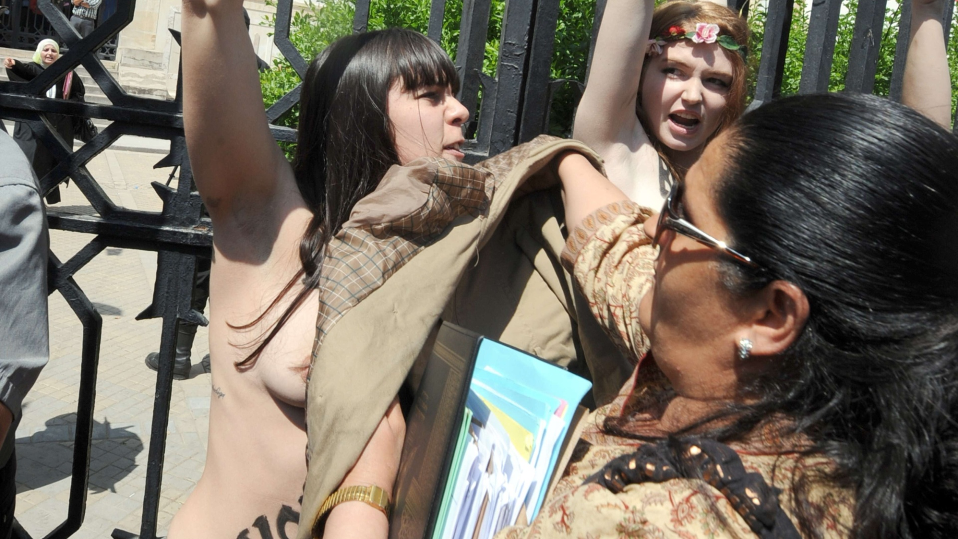 29.mai.2013 - Mulher tenta cobrir seios de manifestante do Grupo Femen, que protestou em frente ao Palácio da Justiça em Túnis, capital da Tunísia. Duas francesas e uma alemã exibiram faixas com os dizeres