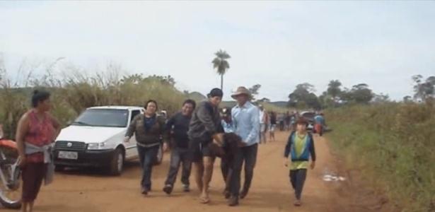 Índios carregam homem ferido durante confronto com policiais na ação de reintegração de posse da fazenda Buriti, em Sidrolândia (67 km de Campo Grande). Um membro da comunidade morreu
