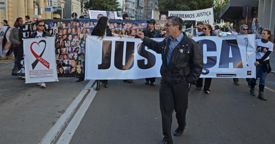 30.mai.2013 - Pais e familiares de vítimas da tragédia na boate Kiss exibem um cartaz com a palavra
