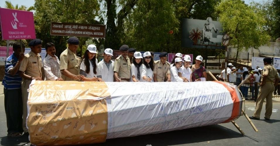 31.mai.2013: Estudantes indianos da Dental College, em Ahmedabad escrevem mensagens em um cigarro gigante enquanto participam do Movimento Deixe o Tabaco no Dia Mundial Sem Tabaco