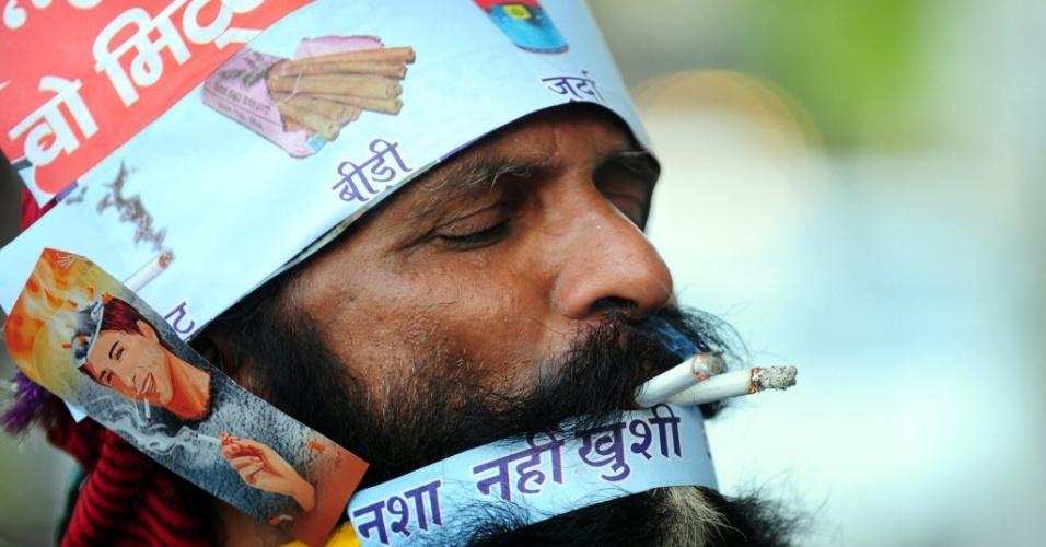 31.mai.2013: O performer indiano Rajendra Kumar Tiwari fuma cigarros enquanto faz sua mágica no Dia Mundial Sem Tabaco, em Allahabad, na Índia
