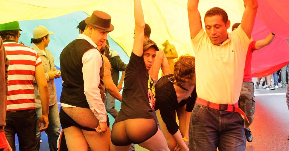 2.jun.2013 - Manifestantes são cobertos pela bandeira das cores do arco-íris, símbolo do movimento LGBT (Lésbicas, Gays, Bissexuais, Travestis, Transexuais e Transgêneros), durante a 17ª edição da Parada Gay de São Paulo, realizada na avenida Paulista, região central da capital