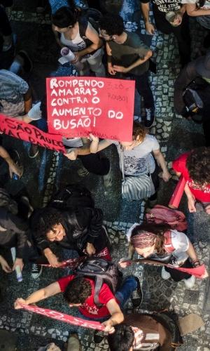 6.jun.2013 - Manifestante exibe cartaz contra o aumento na passagem do ônibus durante protesto realizado no centro de São Paulo, em vias próximas ao viaduto do Chá e Anhangabaú