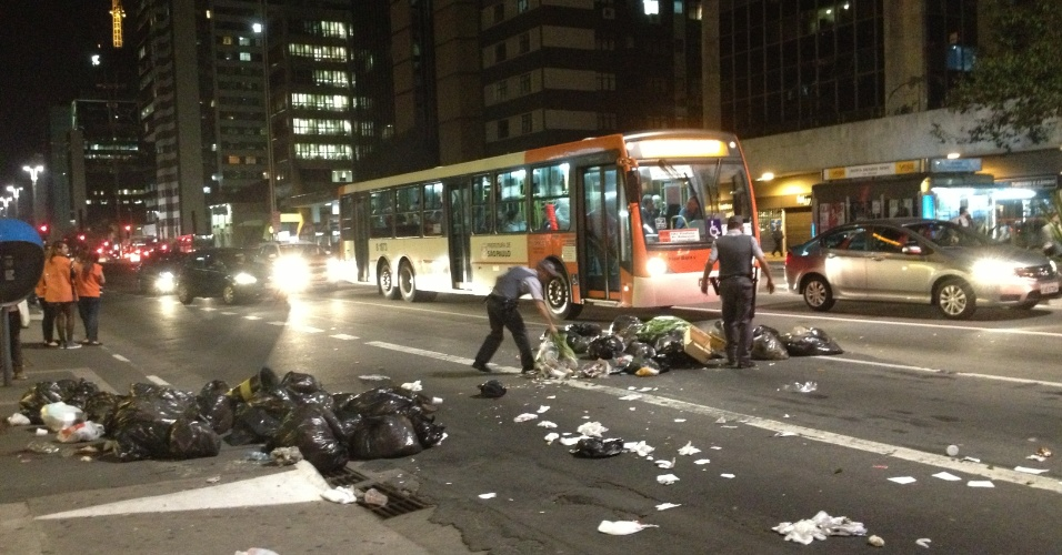 6.jun.2013 - Policiais retiram lixos que obstruem passagem de carros na avenida Paulista, região central de São Paulo, após protesto contra o aumento da tarifa de ônibus de R$ 3 para 3,20