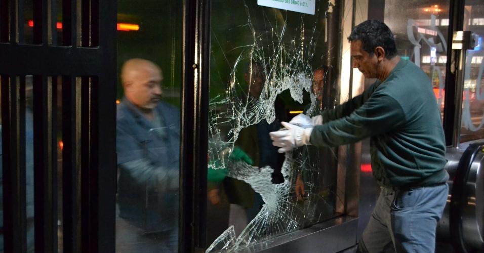 7.jun.2013 - Funcionários manuseiam vidro quebrado na entrada do metrô Trianon Masp após protesto na avenida Paulista, em São Paulo, contra o aumento da passagem de ônibus, na noite desta quinta-feira (6). Segundo a Polícia Militar, 1000 pessoas se reuniram e 15 foram detidas