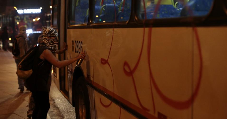 """7.jun.2013 - Manifestante picha ônibus na região do Largo da Batata, na zona oeste de São Paulo (SP), em novo protesto contra o aumento das passagens de ônibus, metrô e trens, nesta sexta-feira. O valor subiu de R$ 3 para R$ 3,20. Manifestantes carregam cartazes, bandeiras e já entregam folhetos com informações sobre o próximo protesto, marcado para as 17h de terça-feira (11) na praça do Ciclista, na avenida Paulista. O tema do protesto é """"Se a tarifa não baixar, São Paulo vai parar"""""""