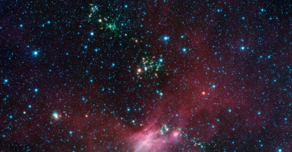 """7.jun.2013 - O telescópio Spitzer registrou estrelas """"bebês"""" (pontos laranjas) arremessando jatos de poeira em uma pequena região da constelação Cão Menor, conhecida por ser uma maternidade do espaço. Alguns desses jatos aparecem como longas faixas verdes, mas, quando ficam encobertos pela poeira, surgem apenas como bolhas esverdeadas. As observações foram feitas pelo Spitzer, telescópio espacial da Nasa (Agência Espacial Norte-Americana), e integram o projeto """"Glimpse 360"""", que busca mapear as estrelas da Via Láctea"""