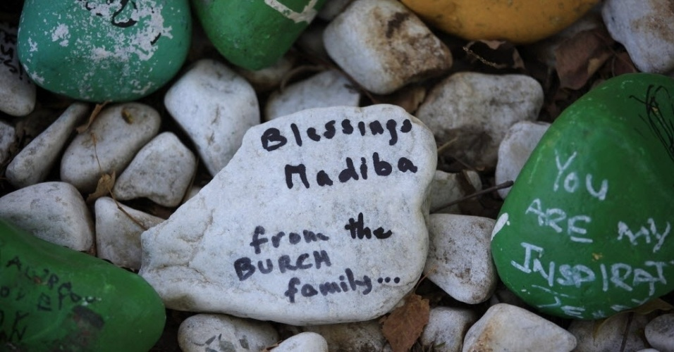 """10.jun.2013 - Pedras com mensagens de apoio são colocadas no jardim na entrada da casa do ex-presidente sul-africano Nelson Mandela, em Johannesburgo. O herói da luta contra o apartheid permanece no hospital pelo terceiro dia seguido com uma infecção pulmonar, e seu estado de saúde continua """"grave, mas estável"""", inalterado desde sábado (8), informou o governo. Na pedra se lê """"Bençãos, Madiba [o segundo nome de Mandela]. Da família Burch"""""""