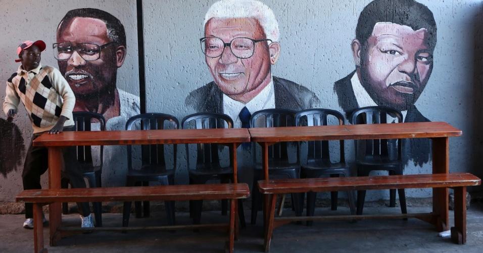 """9.jun.2013 - Homem senta-se próximo a uma parede pintada com retratos do presidente da CNA (Congresso Nacional Africano), Oliver Tambo (esquerda), o ativista anti-aparatheid sul africano, Walter Sisulu, e líder da CNA e ex-presidente da África do Sul, Nelson Mandela, em Soweto, neste domingo (9). Mandela permanece no hospital pelo terceiro dia seguido nesta segunda-feira (10) com uma infecção pulmonar, e seu estado de saúde continua """"grave, mas estável"""", inalterado desde sábado (8), informou o governo"""