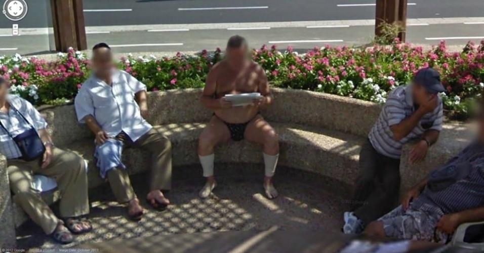 O Google Street View fotografou esse homem lendo jornal bem à vontade em uma praça. Ninguém parece estar incomodado com os trajes ''sumários'' dele