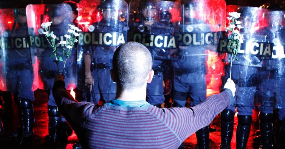 11.jun.2013 - Manifestante mostra flores a policiais militares da Tropa de Choque durante protesto contra o aumento das tarifas em São Paulo
