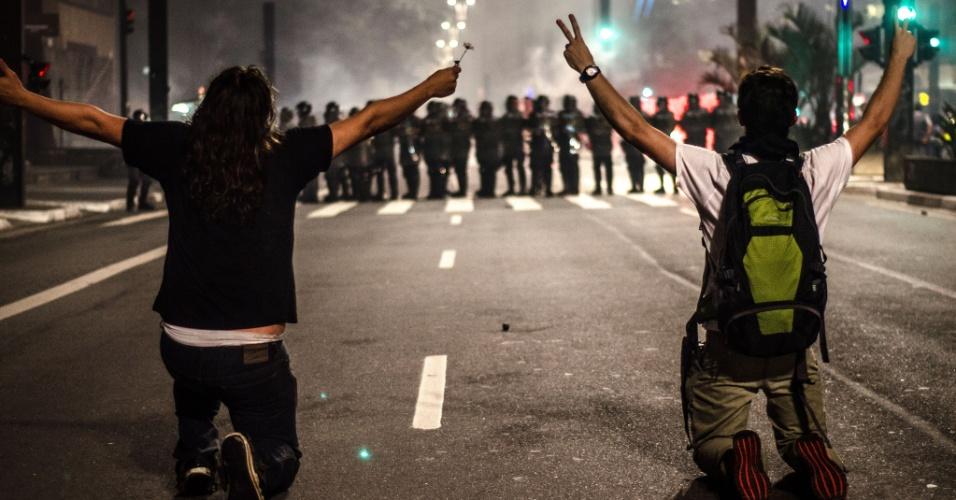 11.jun.2013 - Manifestantes se ajoelham diante de PMs durante protesto na avenida Paulista, em São Paulo. O homem da direita foi atingido por uma bala de borracha na sequência. O da esquerda, mais tarde, detido
