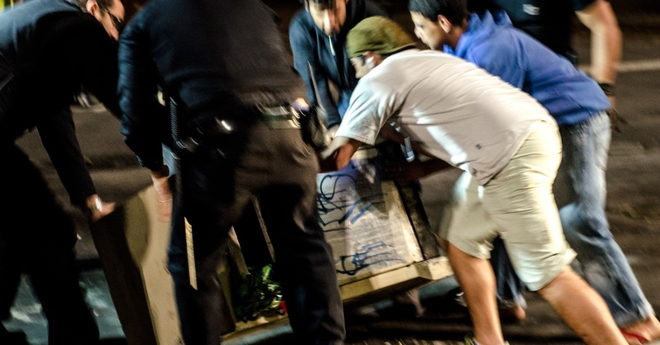 11.jun.2013 - Manifestantes e seguranças do Metrô levantam uma lixeira de concreto, jogada no meio da avenida Paulista durante o protesto